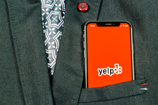 Sankt-Petersburg, Russia, August 24, 2018: Yelp application icon on Apple iPhone X screen close-up in jacket pocket. Yelp app icon. Yelp.com application. Social network. Social media