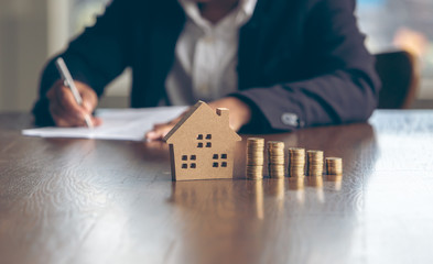 Fototapeta Modeling wooden houses and coins and dollars placed on wooden tables,preparation concept for house model purchase and the fastest growing real estate economy,moving home or renting property via agent obraz