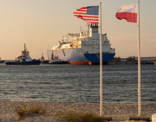 The US and Polish Flags and the American LNG tanker during the supply of liquefied gas to the LNG terminal in Świnoujście in Poland as part of a multi-annual agreement between the USA and Poland