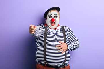 fat clown showing direction with index finger, isolated blue background, studio shot. ha-ha. artist heartly chuckle. close up photo