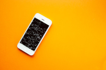 Broken screen of smartphone on the orange background. Smashed glass of cell phone, illustration for repair, fix phone services. Top view with copyspace
