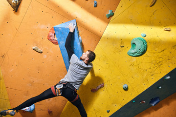 View of motivated active sportsman with physical disability overhanging at large hold, climbing very difficult rock wall, wants to reach the top. Rare view, full length shot.