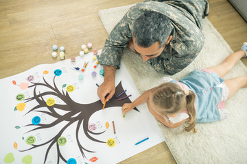 Father and daughter lying on the floor and painting family tree