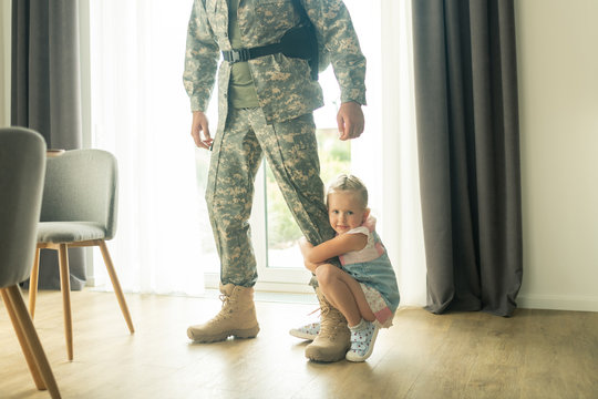 Little blonde girl hugging her father leg while he leaving house