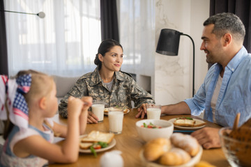 Beautiful female soldier spending morning with husband and daughter