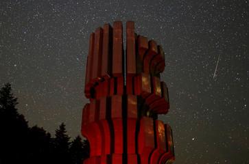 Meteor streaks across skies near the Monument to the Revolution in Prijedor