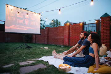 Couple in love watching a movie, in twilight, outside on the lawn in a courtyard