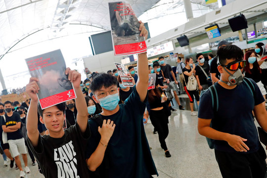 Anti-extradition bill protesters try to get close to the security gates at a mass demonstration after a woman was shot in the eye during a protest at Hong Kong International Airport, in Hong Kong