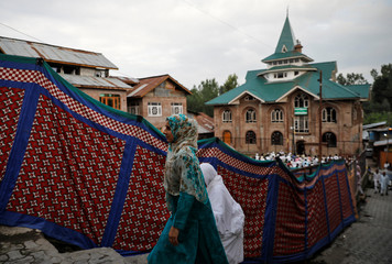 Kashmiri women arrive to offer Eid-al-Adha prayers at a mosque during restrictions after the scrapping of the special constitutional status for Kashmir by the Indian government, in Srinagar