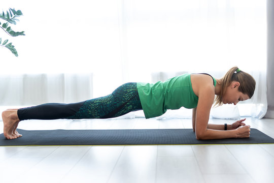 Young sporty woman standing in plank pose on fitness mat