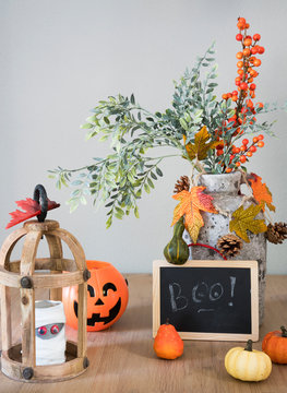 Lantern, pumpkin, bouquet and mummy. Halloween decorations on wooden table