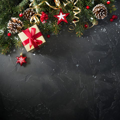 Christmas dark black background with beautiful texture and Golden gift box with red ribbon, serpentine, fir branches, cones, Christmas tree toys stars, top view, copy space.