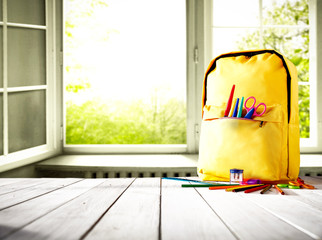 Table background and a schoolbag with some colorful school supplies. Empty space for advertising products and decoration.