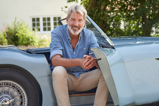 Portrait Of Proud Mature Man Sitting In Restored Classic Sports Car Outdoors At Home