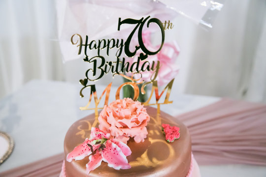 happy 70th birthday mom in rose gold on birthday cake with shoe and handbag fresh flowers