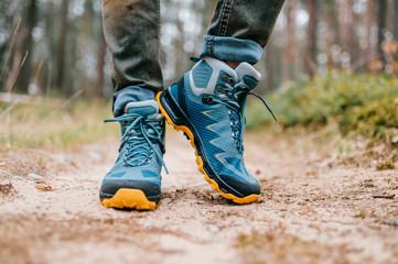 Fototapeta Male legs wearing sportive hiking shoes outdoor. Mens legs in trekking boots for outdoor activity obraz