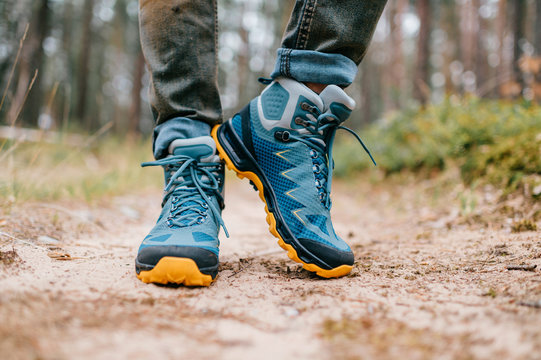 Male legs wearing sportive hiking shoes outdoor. Mens legs in trekking boots for outdoor activity