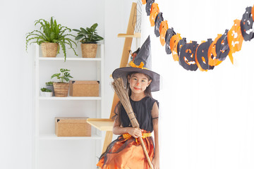 Happy child girl in witch costume to halloween Wall mural