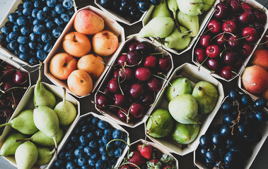 Summer fruit and berry variety. Flat-lay of ripe strawberries, cherries, grapes, blueberries, pears, apricots, figs in wooden eco-friendly boxes over grey background, top view. Local farmers produce Fotobehang