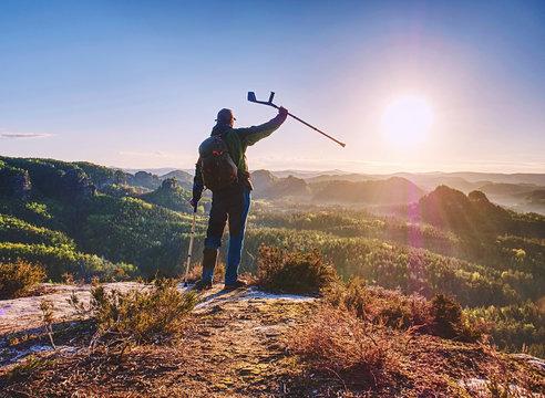 Hiker with medicine crutch achieved mountain peak.