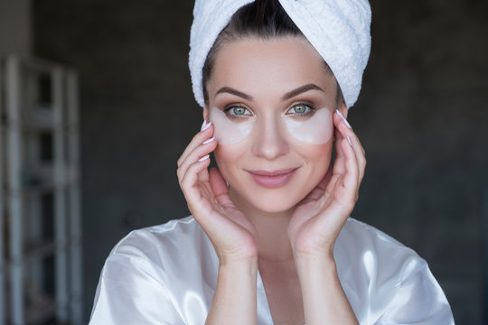 Beautiful fit brunette woman at home in pajama. She do beauty procedures - use patches under her eyes. Natural light. Lifestyle healthcare concept
