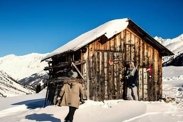 junges blogger pärchen im winterurlaub in den Alpen in Holzhütte