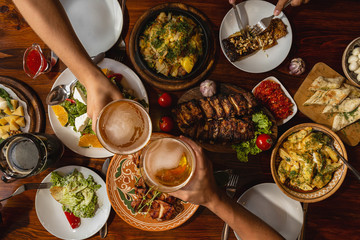 a large wooden table generously covered with delicious national dishes, with friends sitting and drinking light beer from glasses