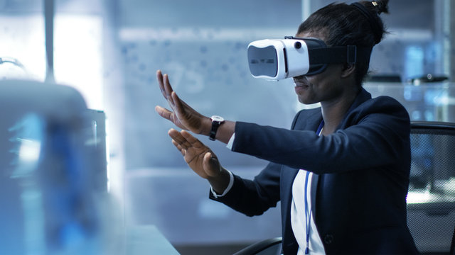 African-American Female Virtual Reality Engineer/ Developer  Wearing VR Headset Creates Content. She's Alone in a Modern Laboratory/ Research Center.