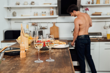 selective focus of shirtless man and table with food and wine glasses on foreground