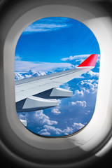 view through airplane window plane flight wing in front of blue white cloud sky. transportation air travel fly concept