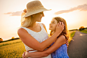 happy family at sunset. Mother and daughter having fun and playing in nature