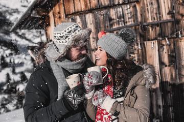 verliebtes Paar im Winter auf Weihnachtsmarkt trinkt Glühwein