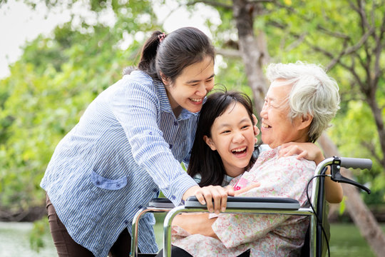 Asian family,senior grandmother,mother,smiling daughter enjoy,hugging in park,patient elderly laugh talk funny with family in wheelchair,happy woman,child girl care with her,love,relationship concept