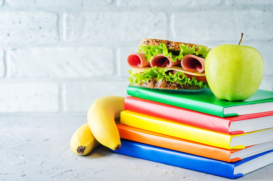 school lunch background with a sandwich, fresh fruits and multicolored books