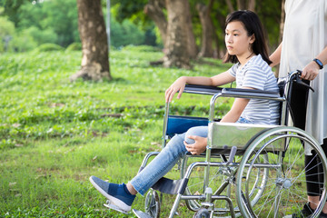 Disabled daughter in wheelchair feeling sad,asian little child girl with depressive symptoms,left leg amputee,crippled,depression,female caregiver or mother care,support in outdoor park,disability