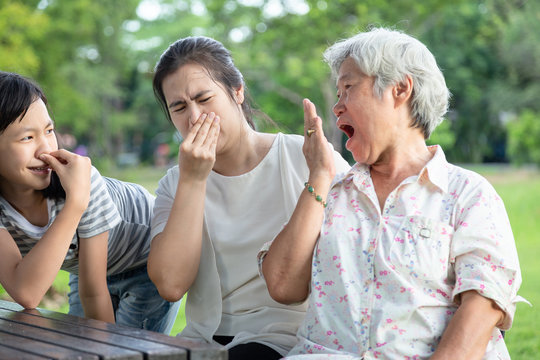 Asian senior grandmother checking breath with her hand,elderly people bad breath,daughter,granddaughter closing her nose,very bad smell,woman and child girl feeling stinks,expression,halitosis concept