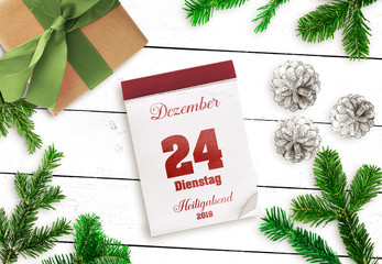 top view of tear-off calendar on December 24 Christmas Eve 2019, in German language, on white wooden table