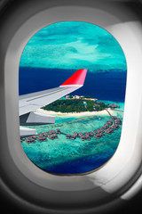 view through airplane window on plane flight wing in front of tropical island indian ocean maldive. transportation vacation air travel fly concept