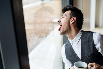Young man with coffee standing by the window, sticking out tongue.