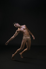 Naked athletic man standing and extending hand