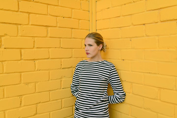 Outdoors portrait of beautiful young woman, she posing against yellow brick wall.