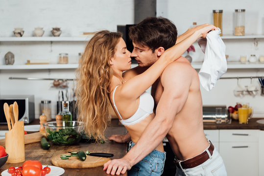 side view of sexy couple kissing and embracing in kitchen