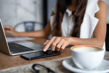 Female businessmen are using smartphone and laptop to work in office.