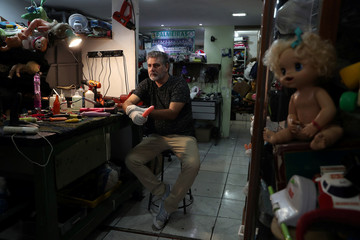 Bartolomeu Queiroz de Alencar, a toys repairman who became also a sex toys repairman, poses for a picture with a vibrator in his workshop in Osasco
