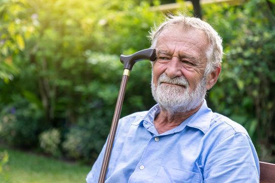 Thoughtful depressed senior old caucasian man holding cane sitting in garden