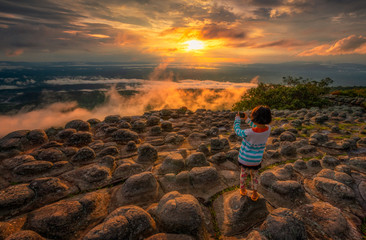 Asian girls take pictures of beautiful sunsets at the highest point of Phu Hin Rong Kla National Park and the rock fields on the northern summit of Thailand.
