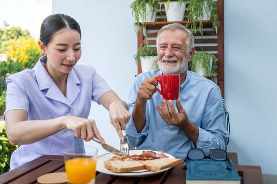 Nurse assist elderly senior man to eat breakfast and drink coffee with mug in hand at nursing home