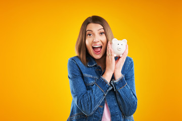 Close up of woman in denim jacket holding piggy bank over yellow background
