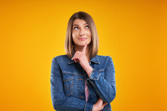 Close up of woman in denim jacket thinking and pointing over yellow background
