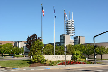STONY BROOK, NY - MAY 24, 2015: Stony Brook University Main Entrance. The sign and flags with the Wang Center in the background at the SUNY  institution at Stony Brook, Long Island, New York.